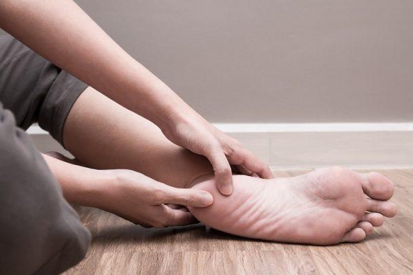 Kvinna med ont i hälen pga hälsporre